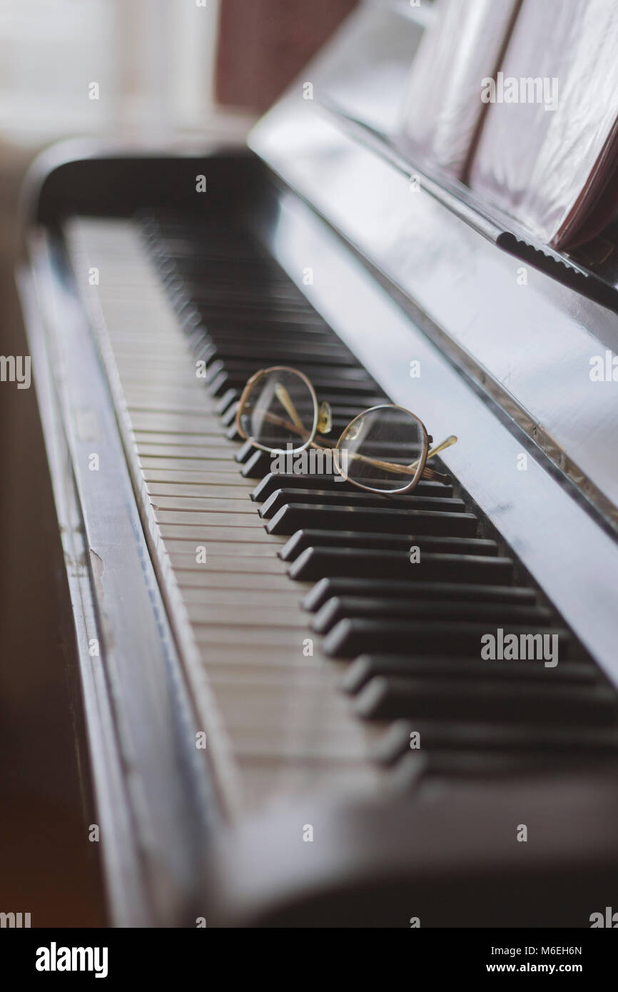 Glasses lying on the keys of a piano - Stock Image