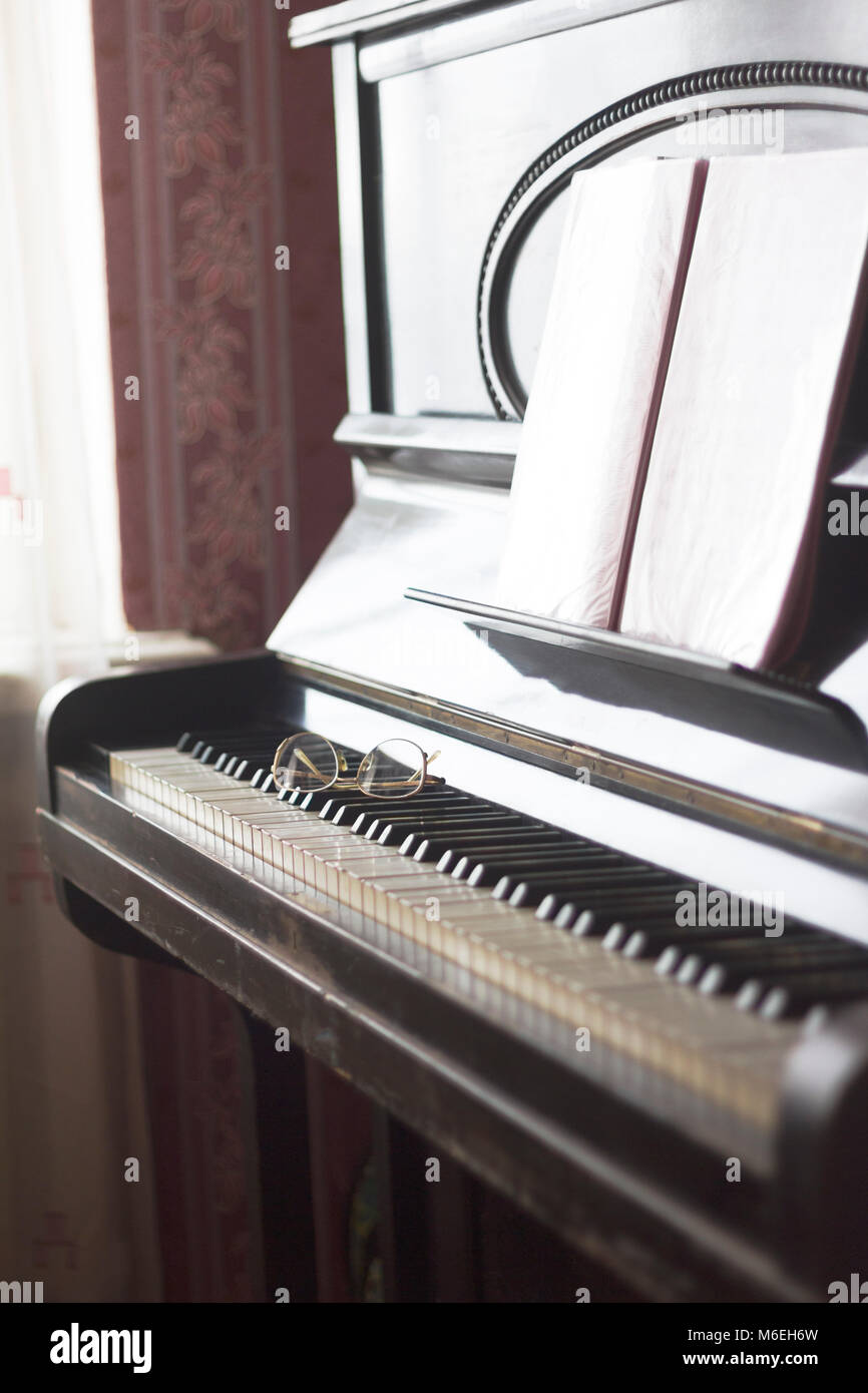 Old piano with sheet music and spectacles lying on the keyboard - Stock Image