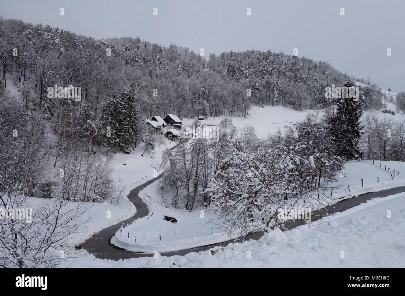 Snow covered landscape with a homesteade in wintertime. Savinjska region ; Stajerska (Steiermark) Slovenia - Stock Image