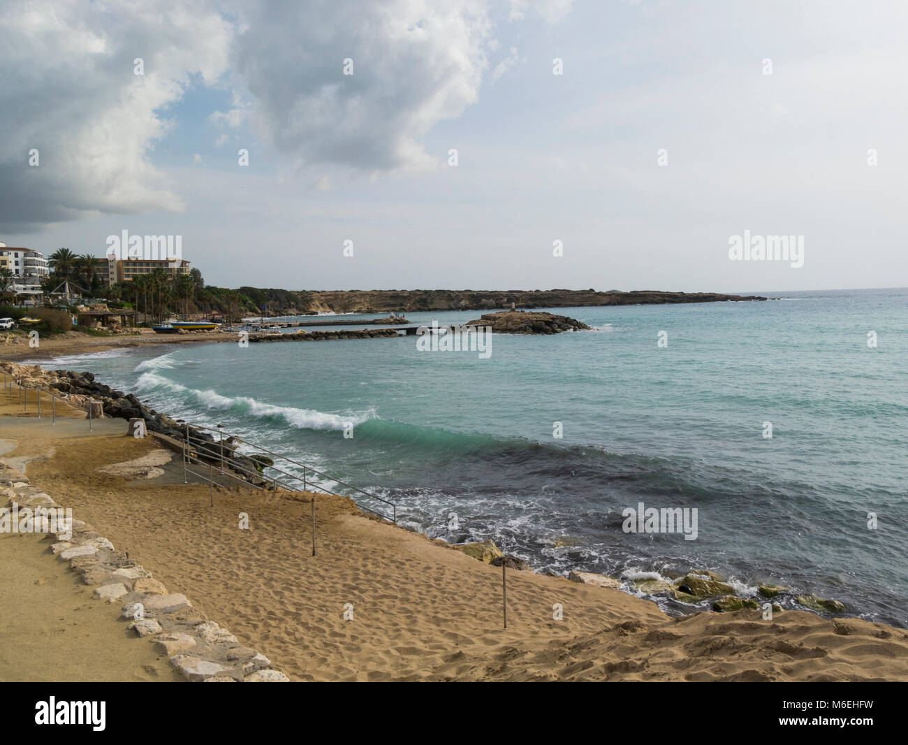 Looking along coastline at Coral Bay Cyprus with Mediterreaneum sea pounding the rocks popular tourist resort in - Stock Image