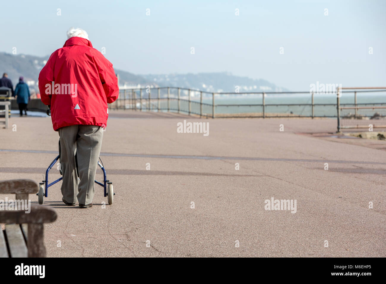 An old man with a walking aid on a seafront walk - Stock Image