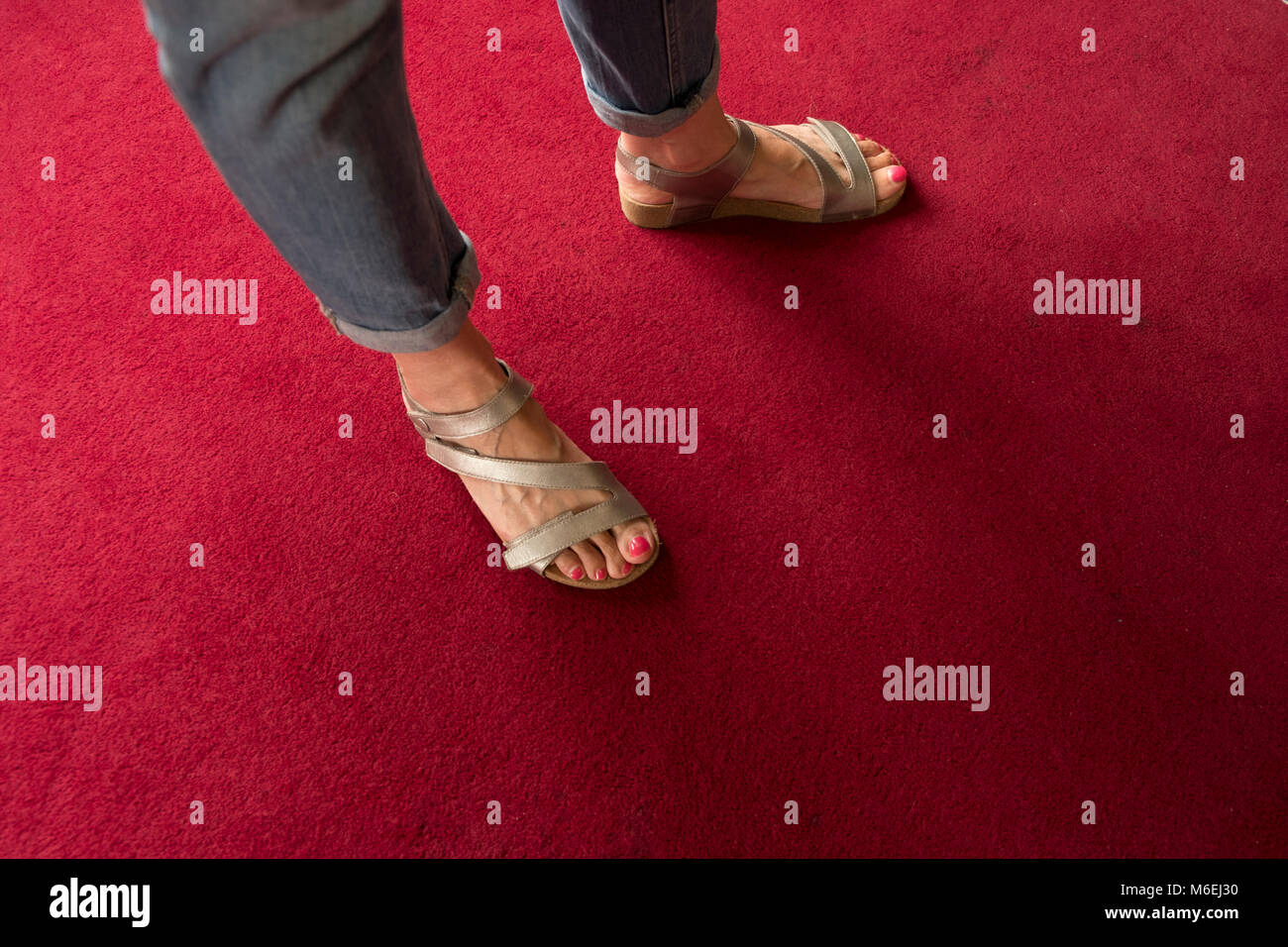 Feet with red nail varnish in silver sandles in a bright red carpet. - Stock Image