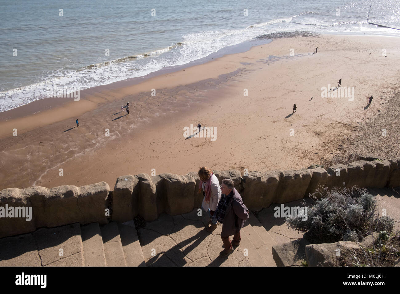 People walk on the sandy beach  with their dogs and up the cliff steps at Ramsgate as the tide recedes. - Stock Image