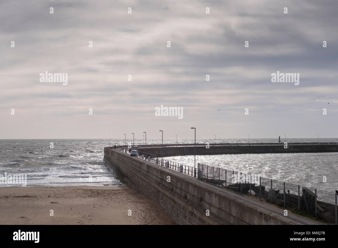People walk on the habour wall road as the tide comes in on a sunny day in  Ramsgate, Kent - Stock Image