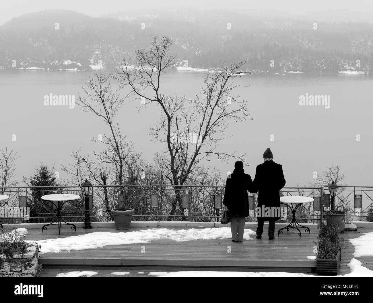 Elder Couple holding each other while standing and staring the cold lake. Greece - Stock Image
