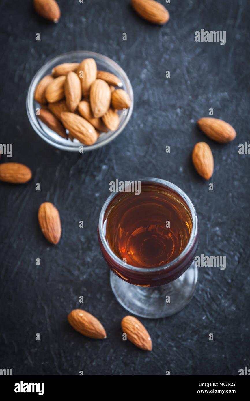 Italian liqueur Amaretto with almonds on black stone background, copy space Stock Photo