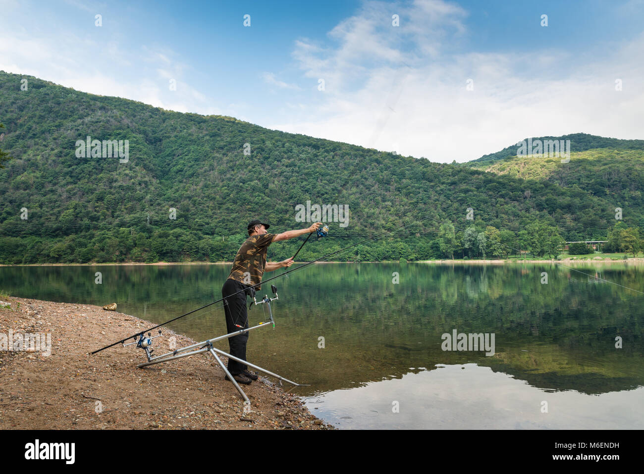 Fishing adventures, carp fishing. Angler with camouflage t-shirt and a fishing rod in his hand, is casting the bait - Stock Image