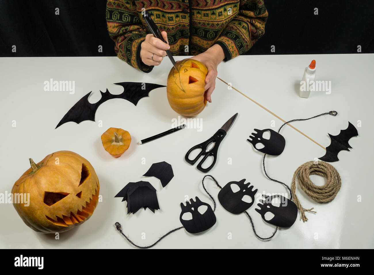 Making halloween decorations including paper figures, skulls and cutting scary faces of pumpkins Stock Photo