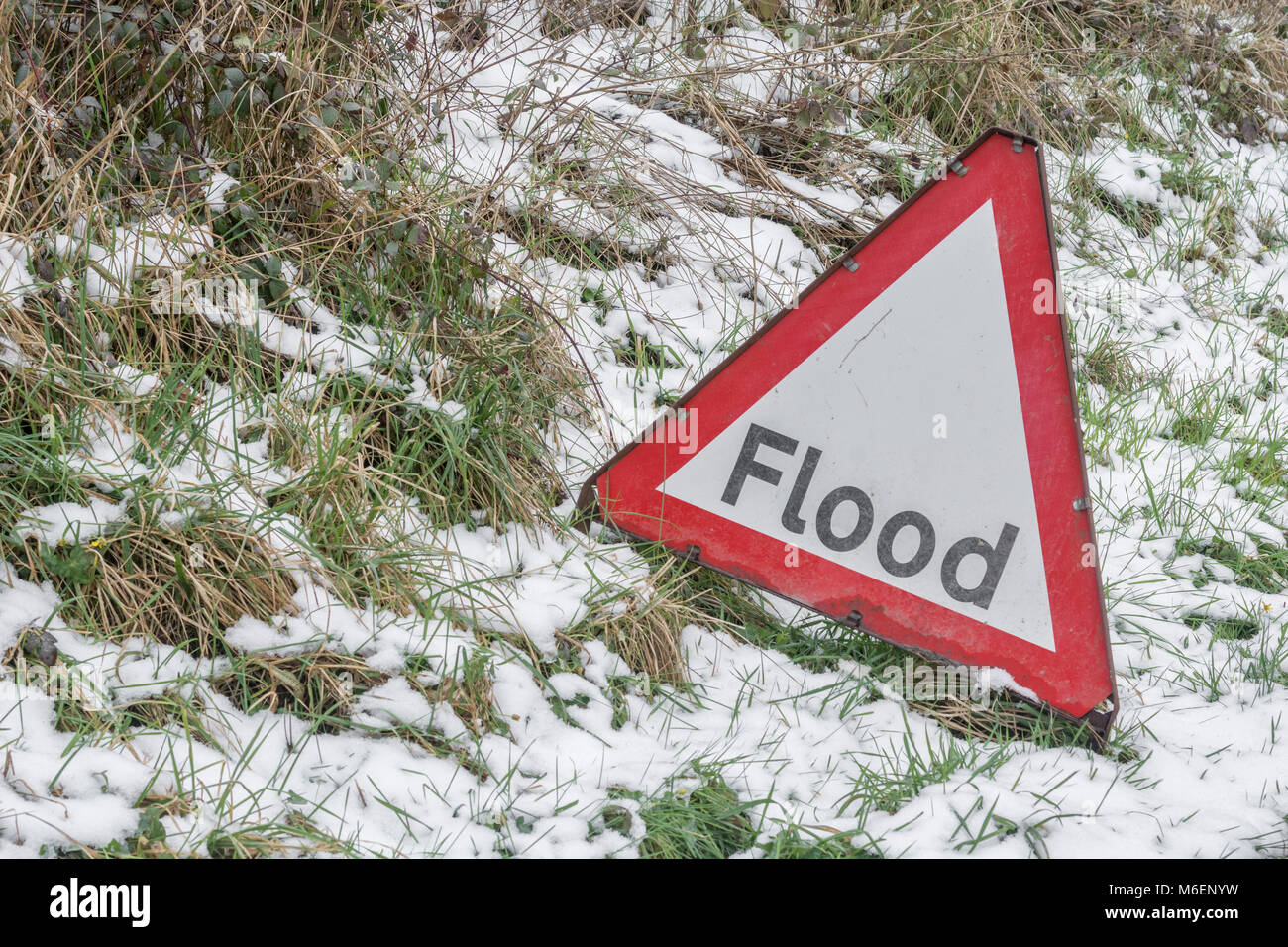 The anomaly of a red flood warning road sign during the snows of the 2018 'Beast from the East'  - in Lostwithiel, - Stock Image