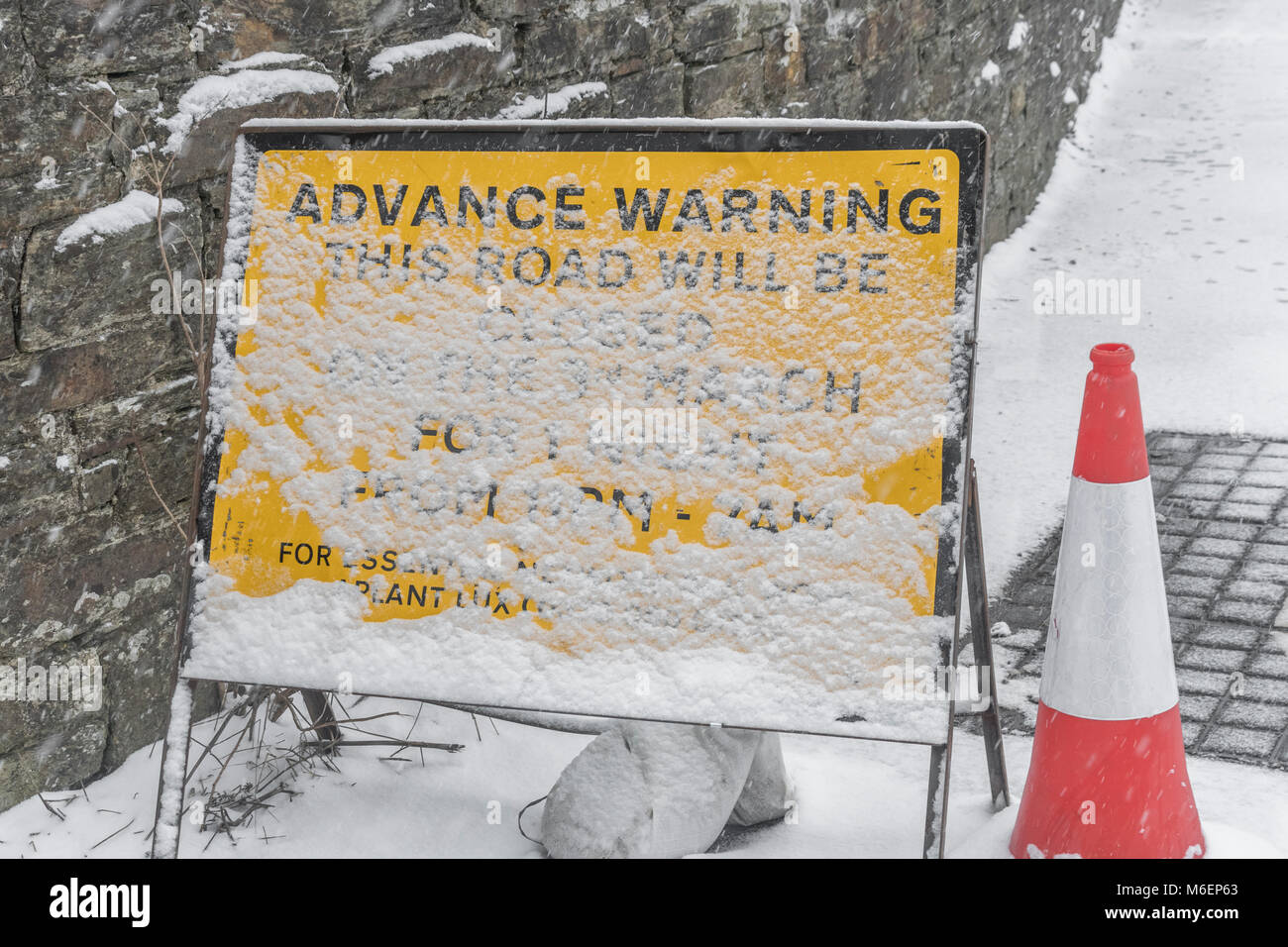 Advance warning roadworks sign covered with sticking snow. - Stock Image