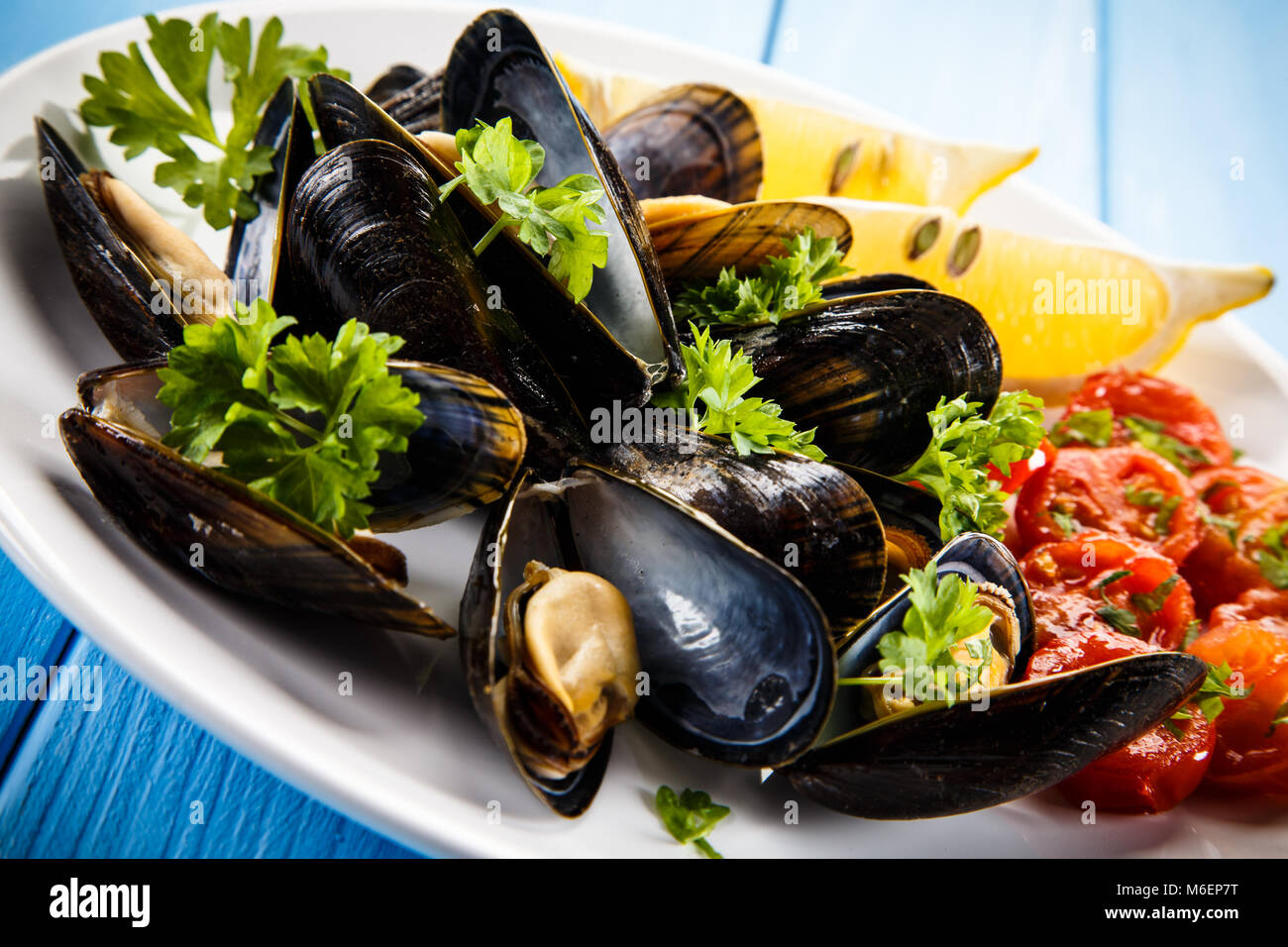 Cooked mussels with lemon and cherry tomatoes - Stock Image