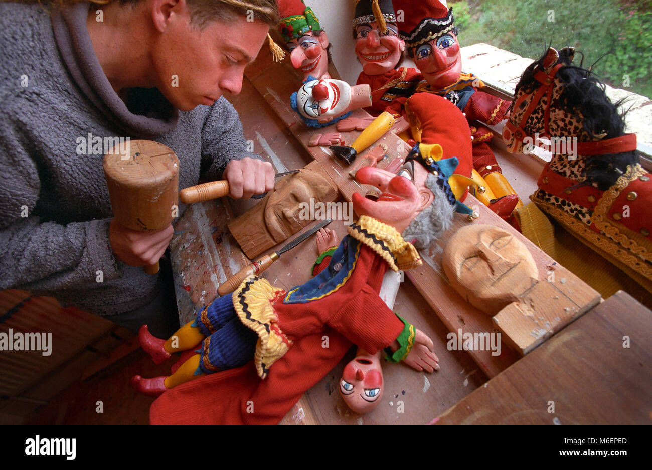 Devon, UK. Professor Mark Poulton making Punch and Judy puppets with wood carving tools. - Stock Image