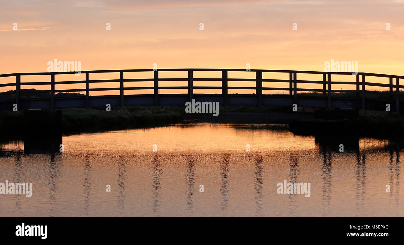 Colour photograph of footbridge backlit by sunrise crossing bridge over Afon Crigyll at Rhosneigr on the western - Stock Image