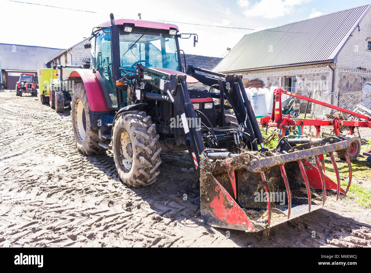 Agricultural machinery and equipment . Tractor with front loader for manure. The yard of a dairy farm. Podlaskie, - Stock Image