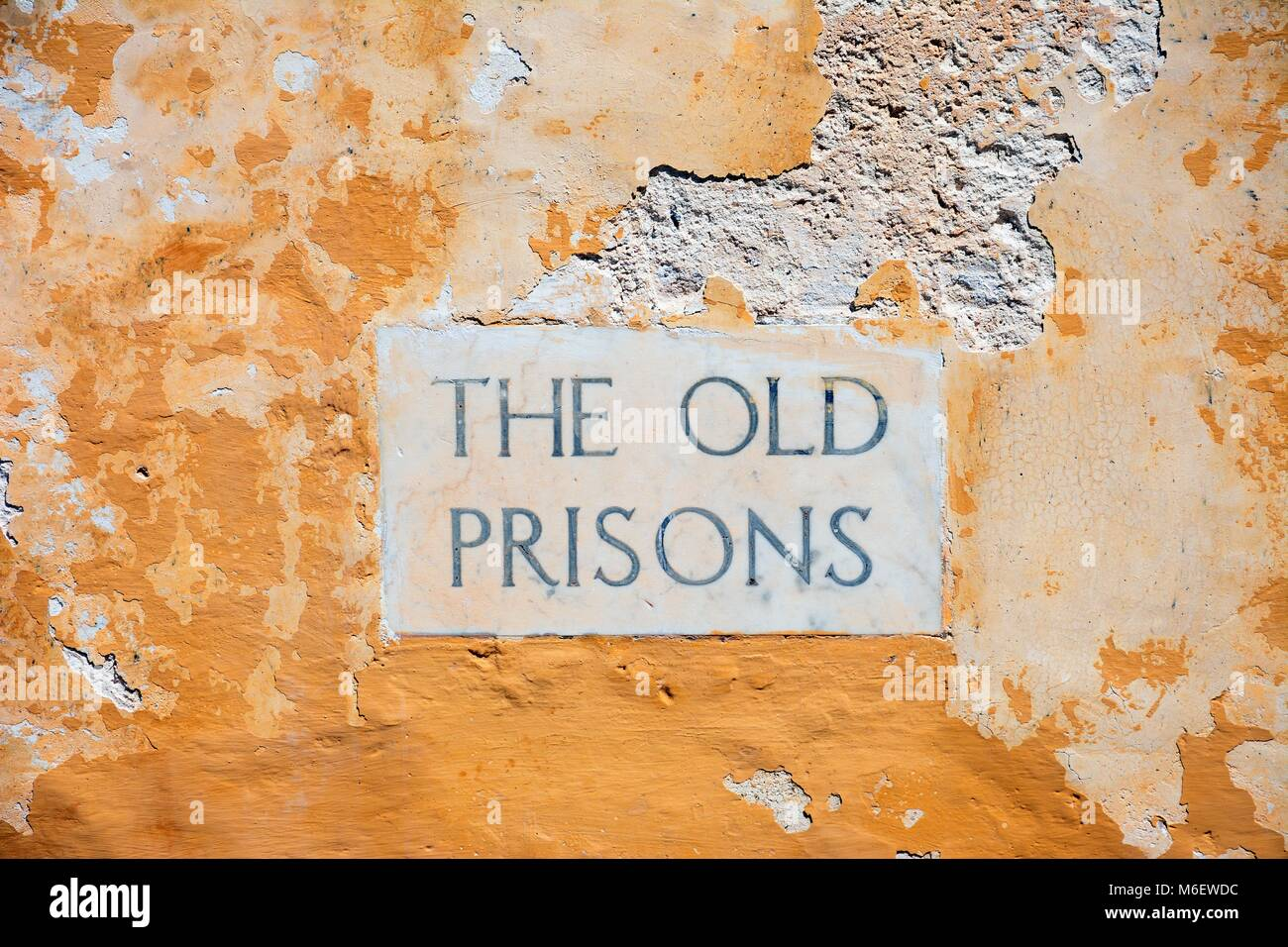 The Old Prisons sign embedded in a building wall within the citadel, Victoria (Rabat), Gozo, Malta, Europe. - Stock Image