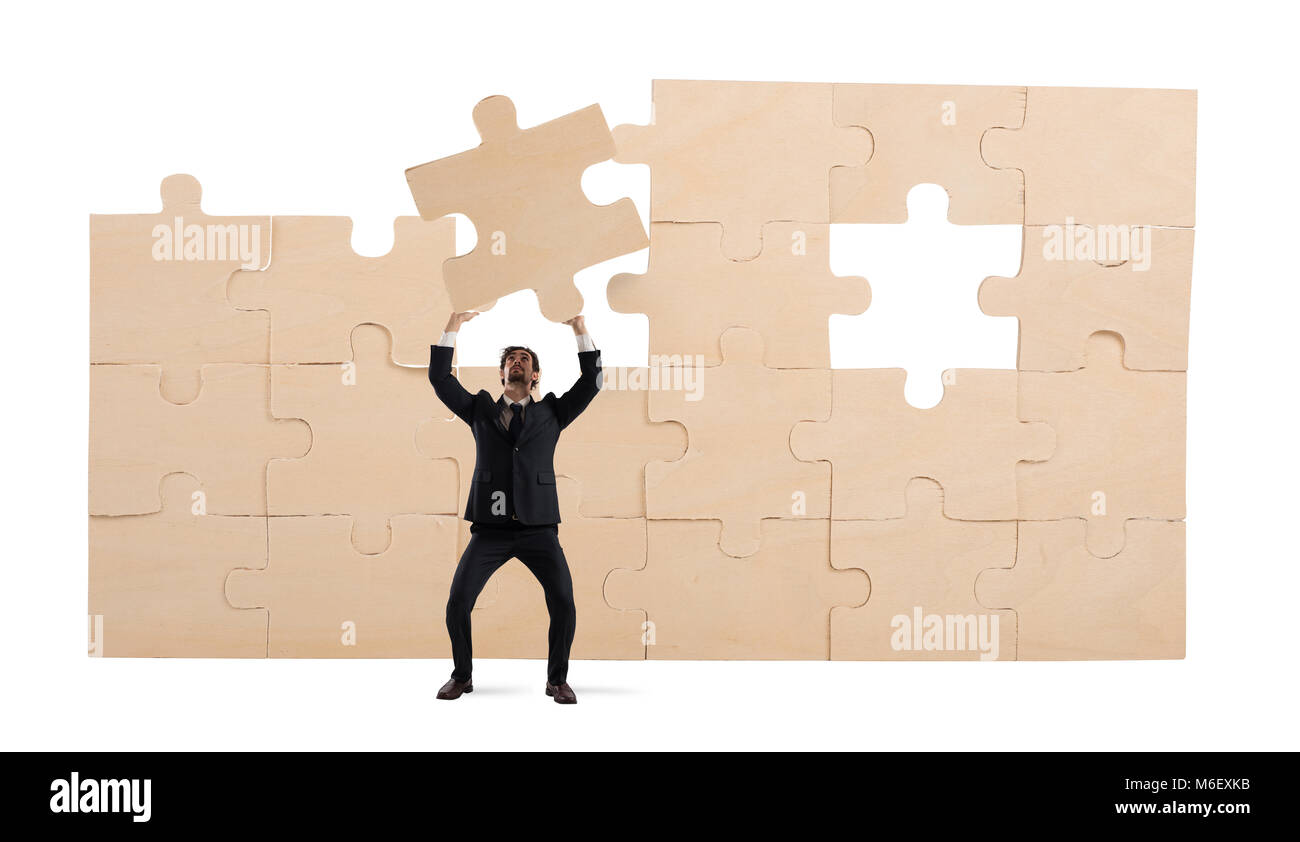 Businessman with a piece of puzzle. Build the business concept - Stock Image