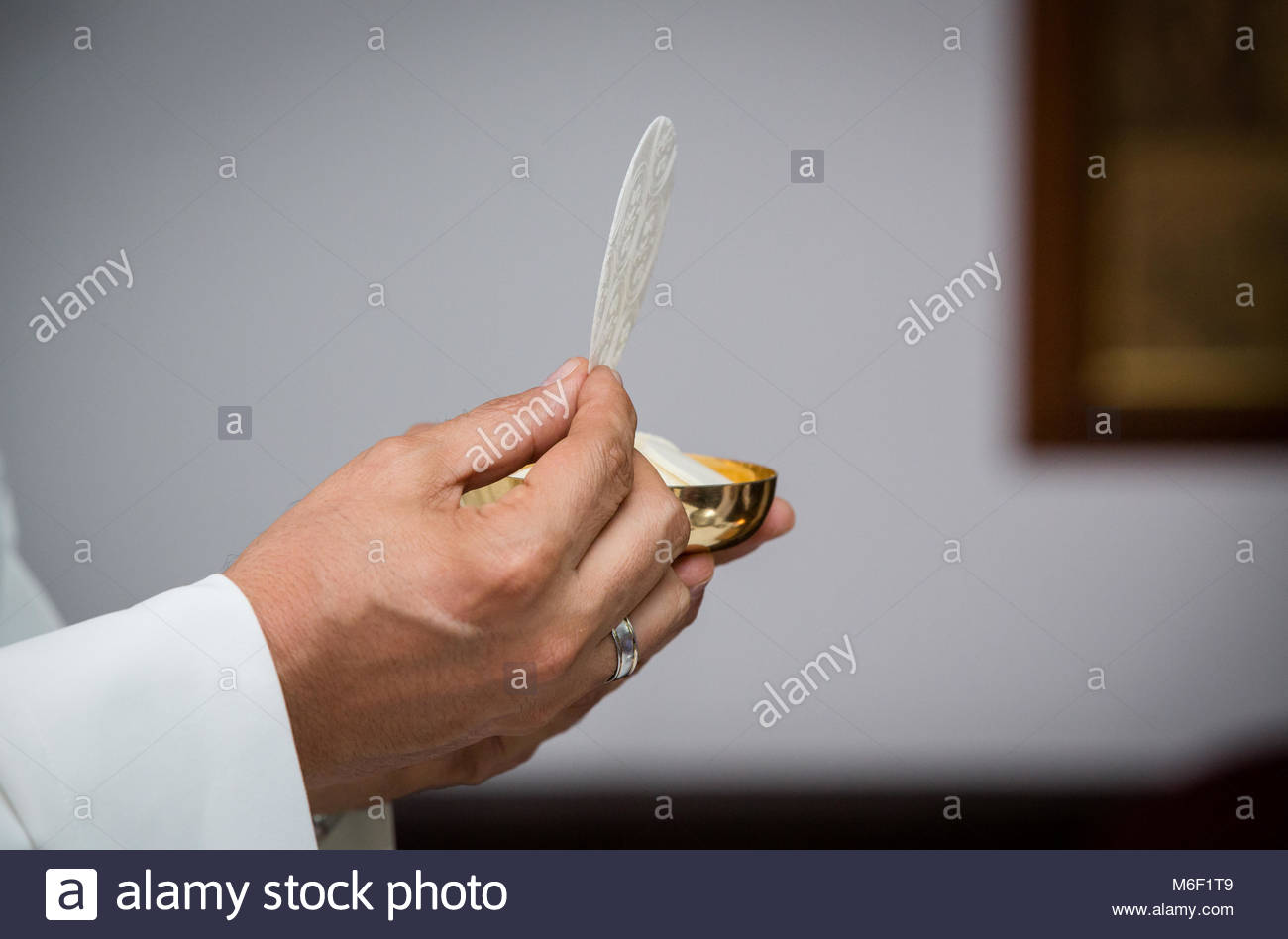 Closeup of priest with communion in the hand. Religious ceremony. Holy communion on a catholic mass. Concept: Free Stock Photo