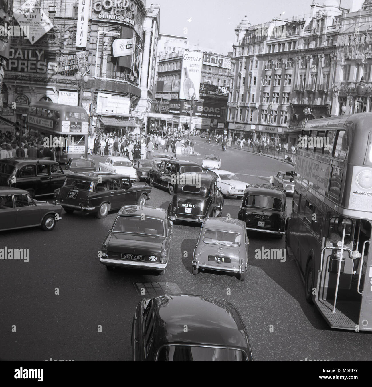 1960s, historical picture, traffic congestion as vehicles converge at the entrance to a busy and crowded Shaftesbury - Stock Image