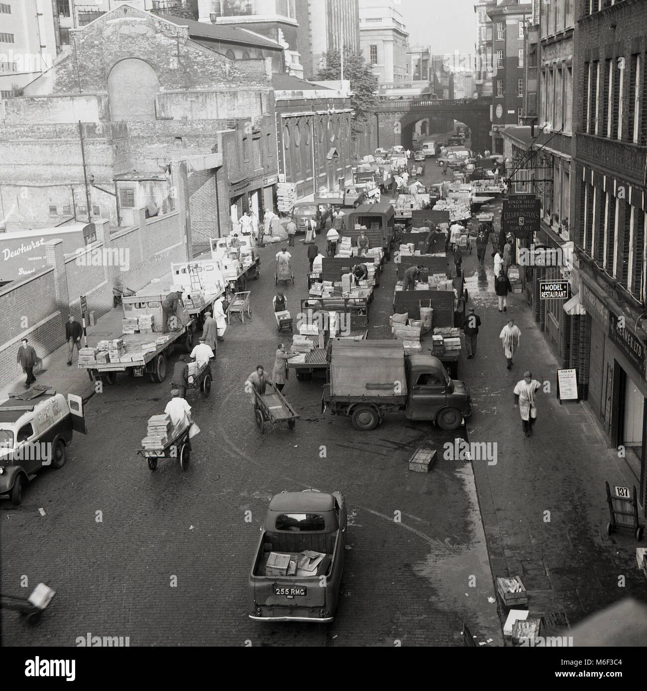 1960s, historical picture showing porters with wheelbarrows working in a street next to the long established fruit - Stock Image