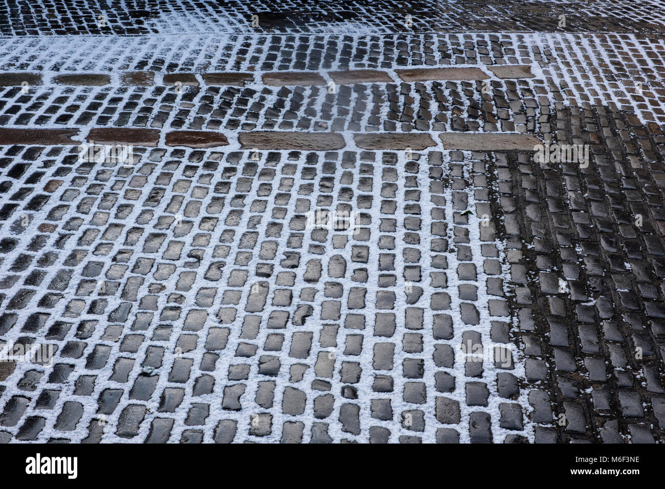 Snow covered cobbles on an icy road in central london. Icy roads in winter and slippery precautions. Cobbled streets - Stock Image