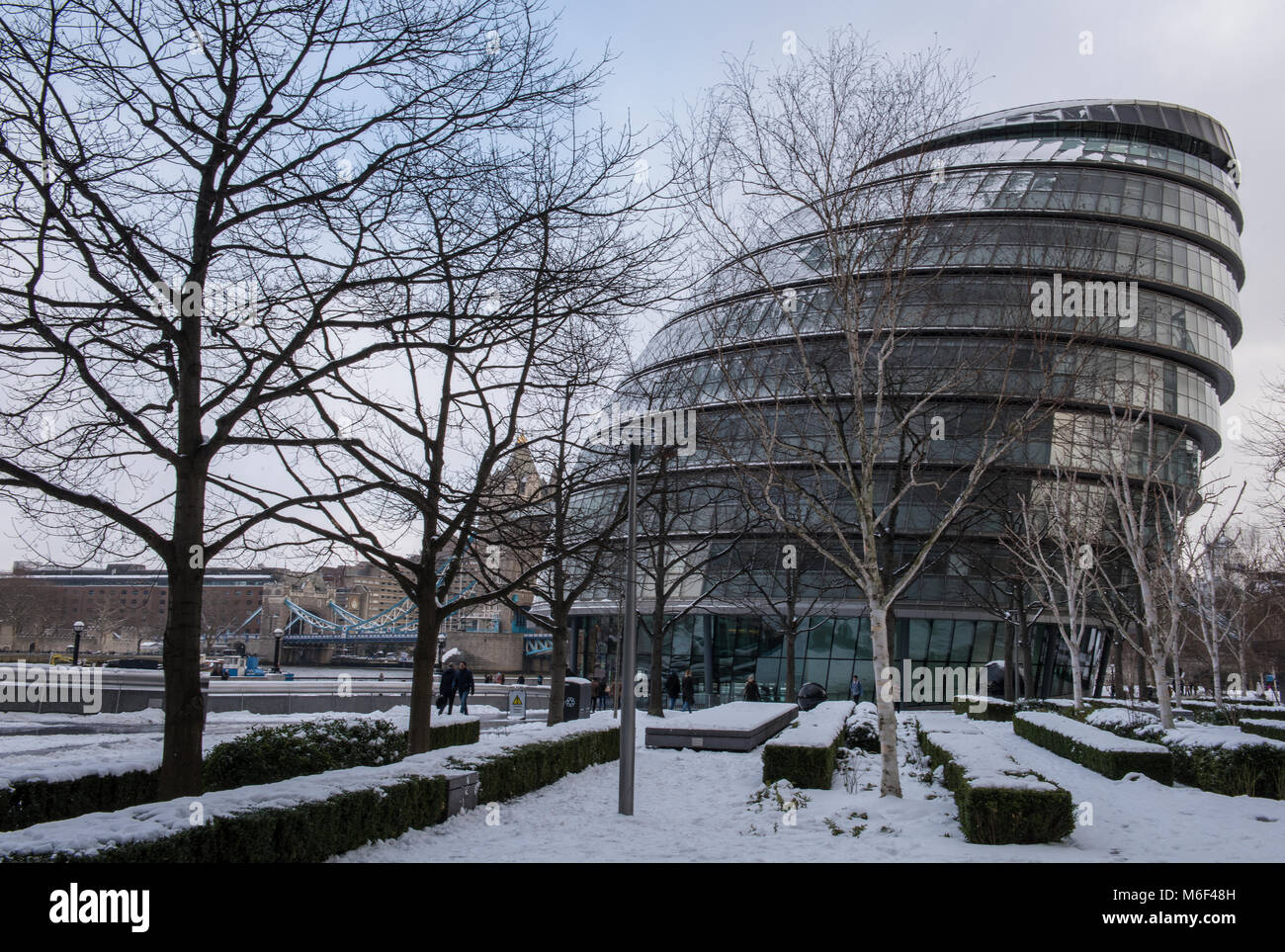 city hall the home of greater london council or GLC in the snow at more london place on the banks of the river thames - Stock Image