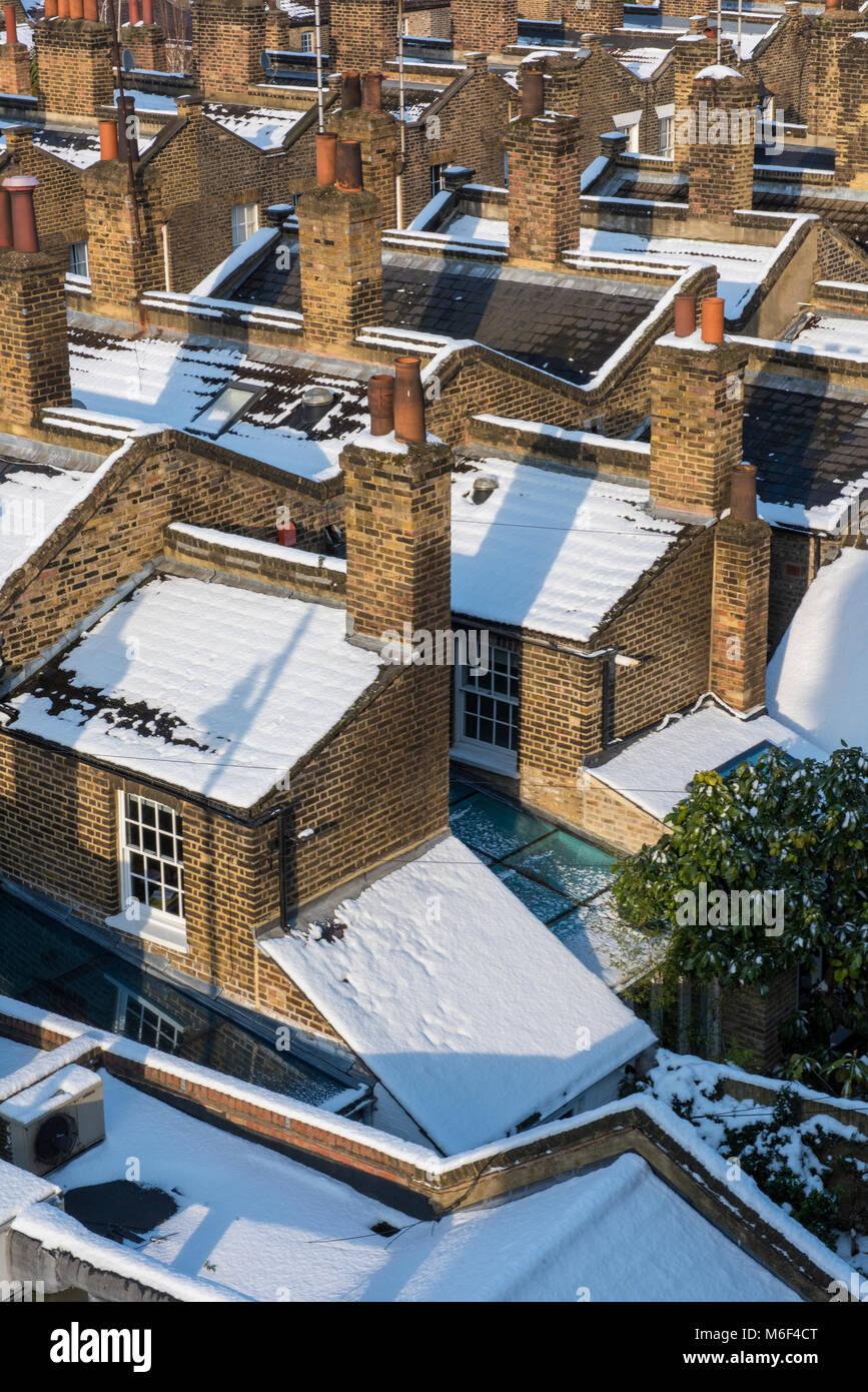 Rows of terraced homes or houses with their rooftops covered in snow after a winter seasonal storm and snowfall - Stock Image