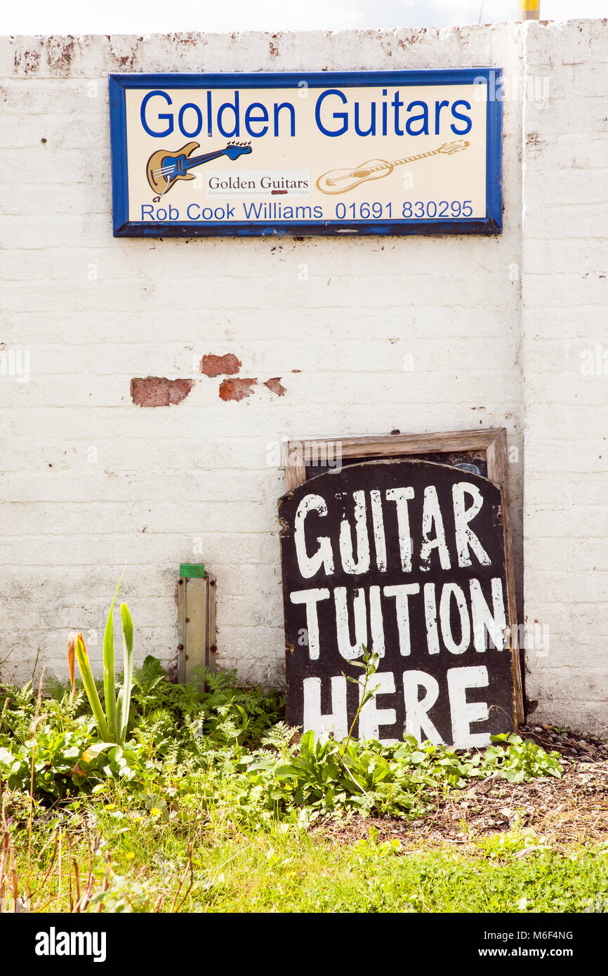 Sign on the wall of  the side of a house advertising guitar tuition from Golden Guitars - Stock Image