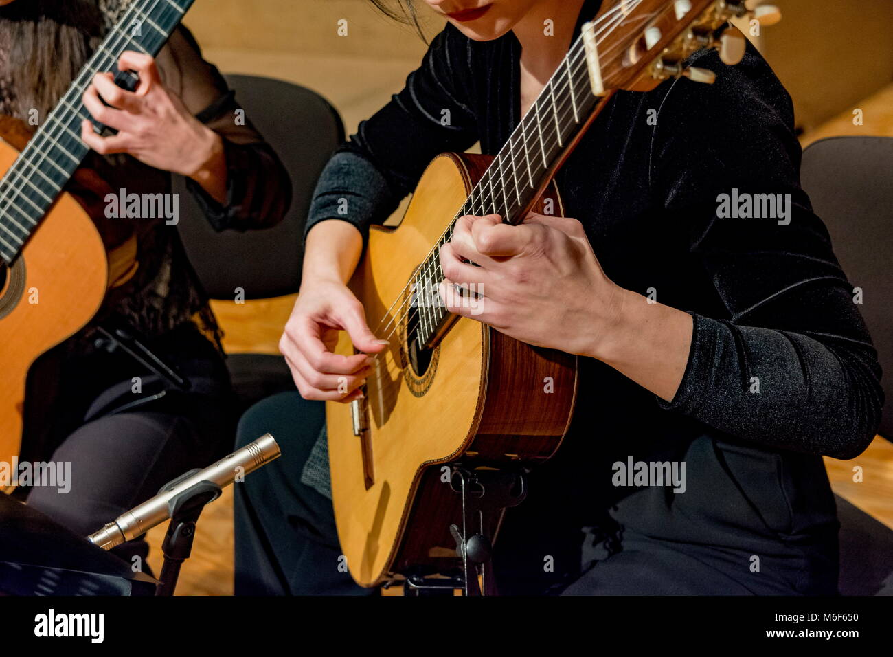 two young women playing guitar in a concert - Stock Image