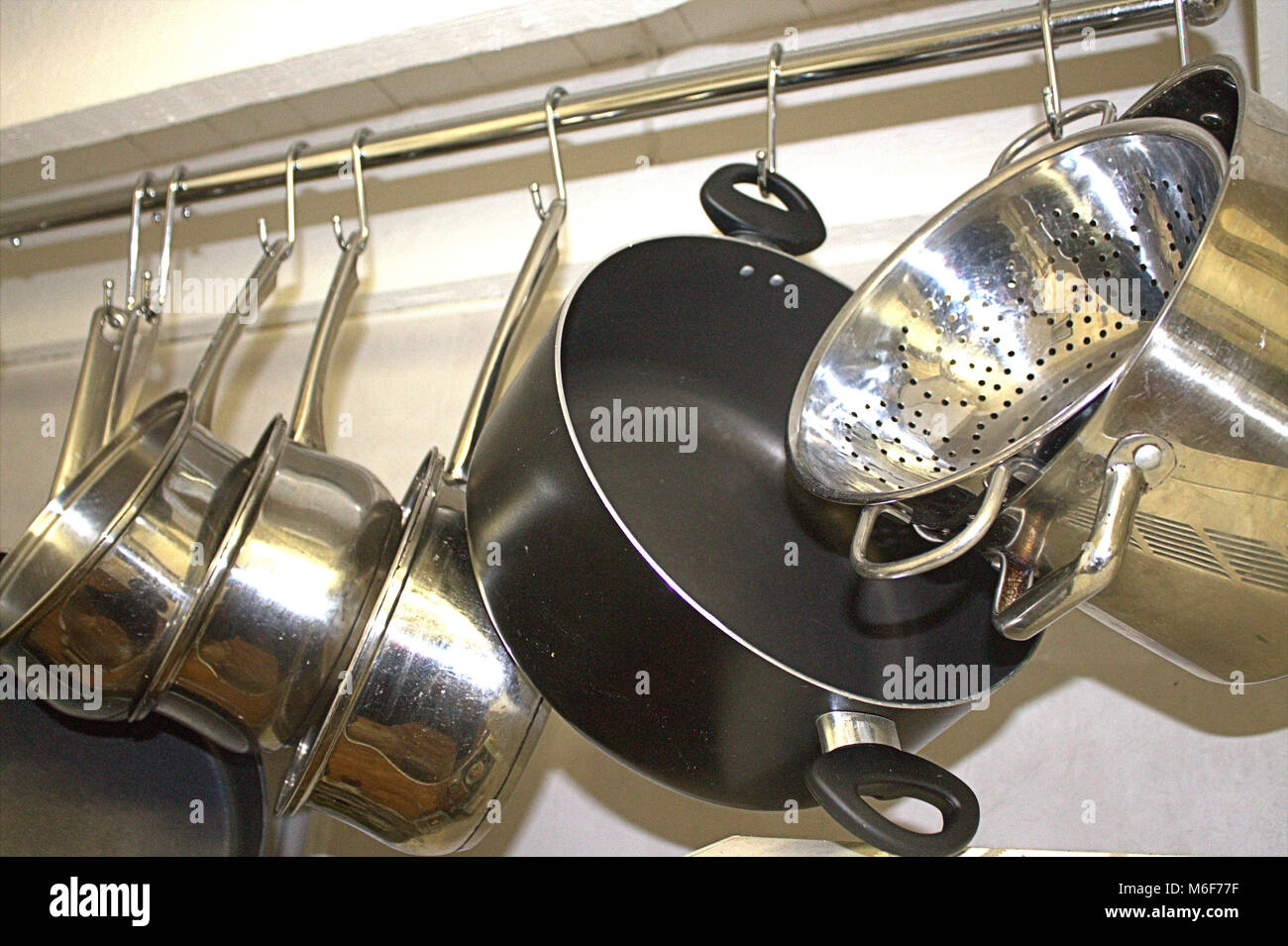 Pots and Pans hanging on a rail in a domestic kitchen - Stock Image
