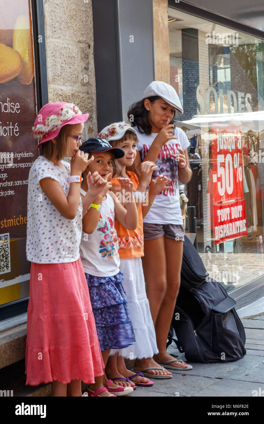 Vanne, Farnce.  A group of children stand behind a street performer pretending to play a musical instruments - Stock Image