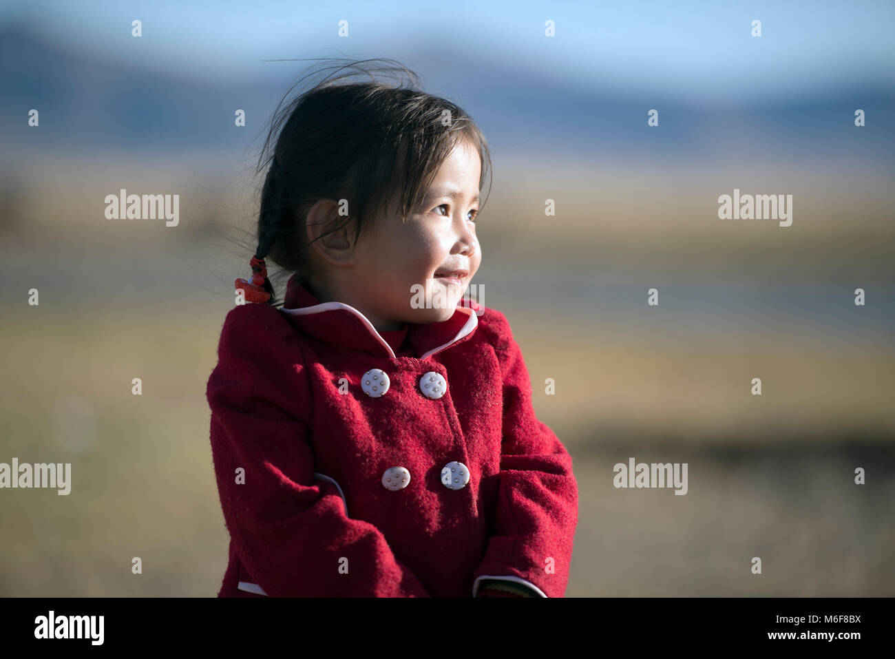 A young, indigenous, Kazakh nomad gir dressed warm for the coming onset of winter. Altai Mountains, Mongolia. - Stock Image