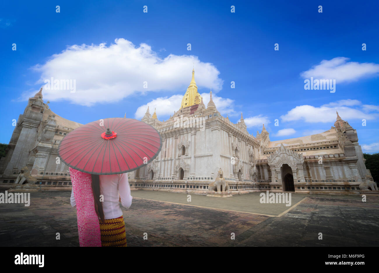 Woman Myanmar holding traditional red umbrella on the Ananda temple at daytime in Bagan, Myanmar. - Stock Image