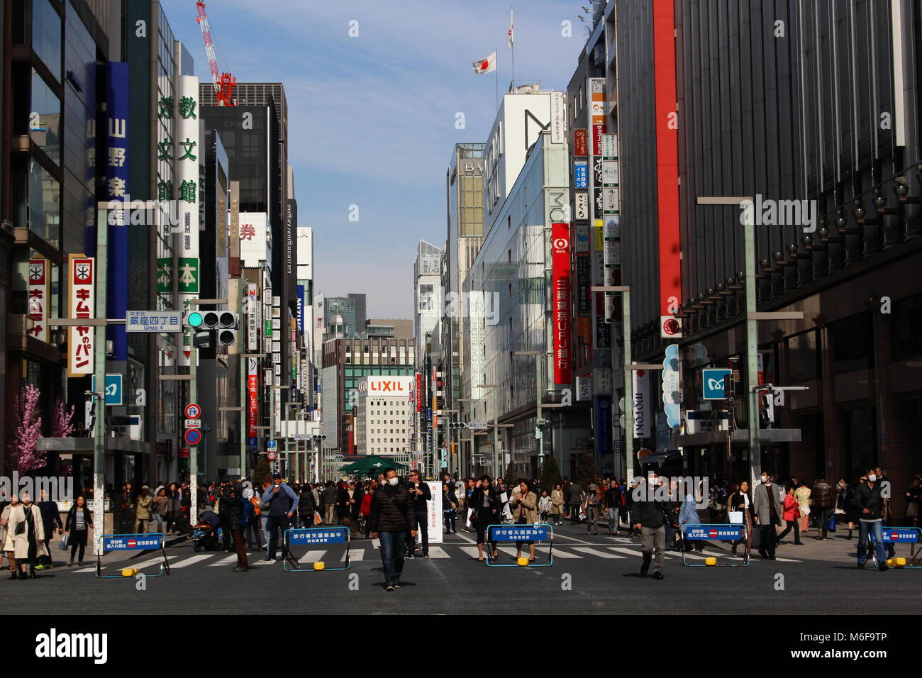 A busy crossing in Ginza in central Tokyo. It's a so-called 'pedestrian paradise day' so some roads - Stock Image