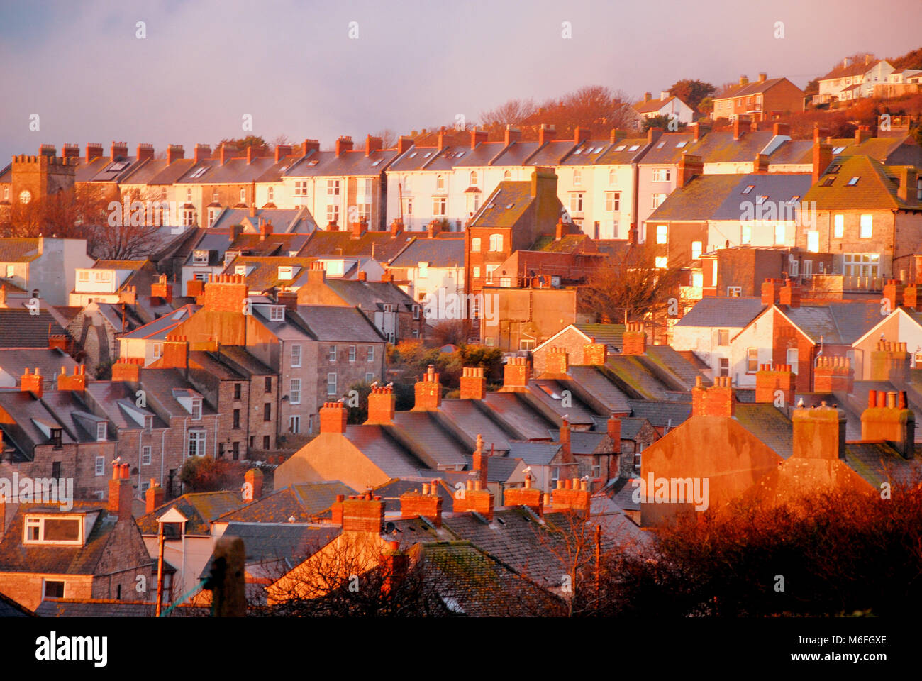 Portland, Dorset. 3rd March 2018 - A glorious sunset bathes the Portland village of Fortuneswell in a peachy glow - Stock Image