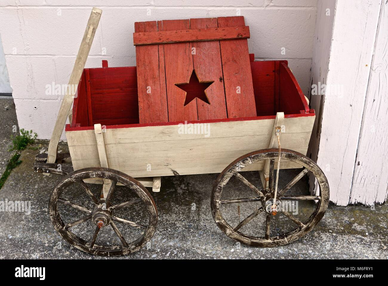 Vintage Wooden Toy Wagon And A Red Wood Door With A Star Cut Into It Stock Photo Alamy