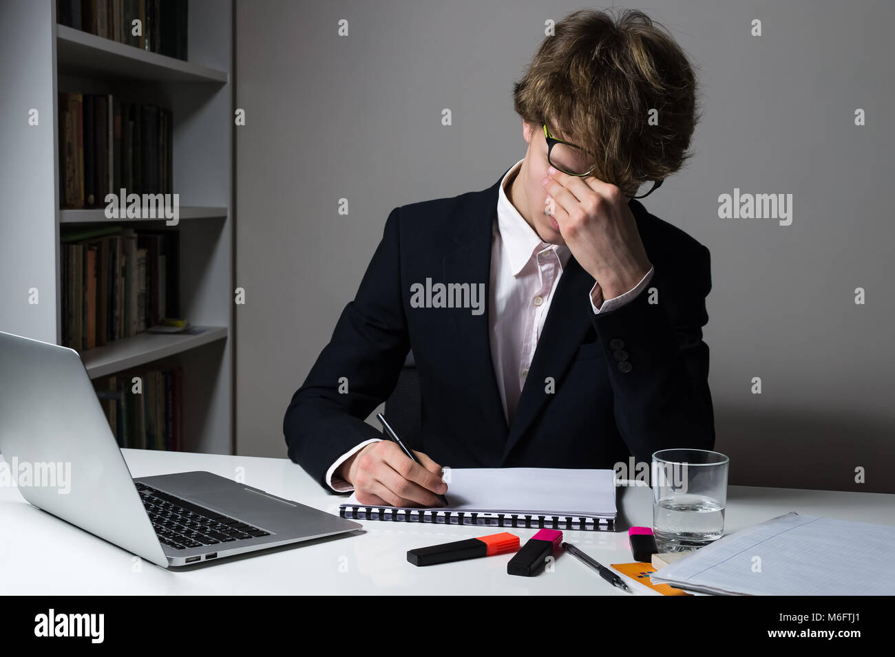 Exhausted employee or student in official suit working late hours at modern desk to meet deadline for assignment - Stock Image