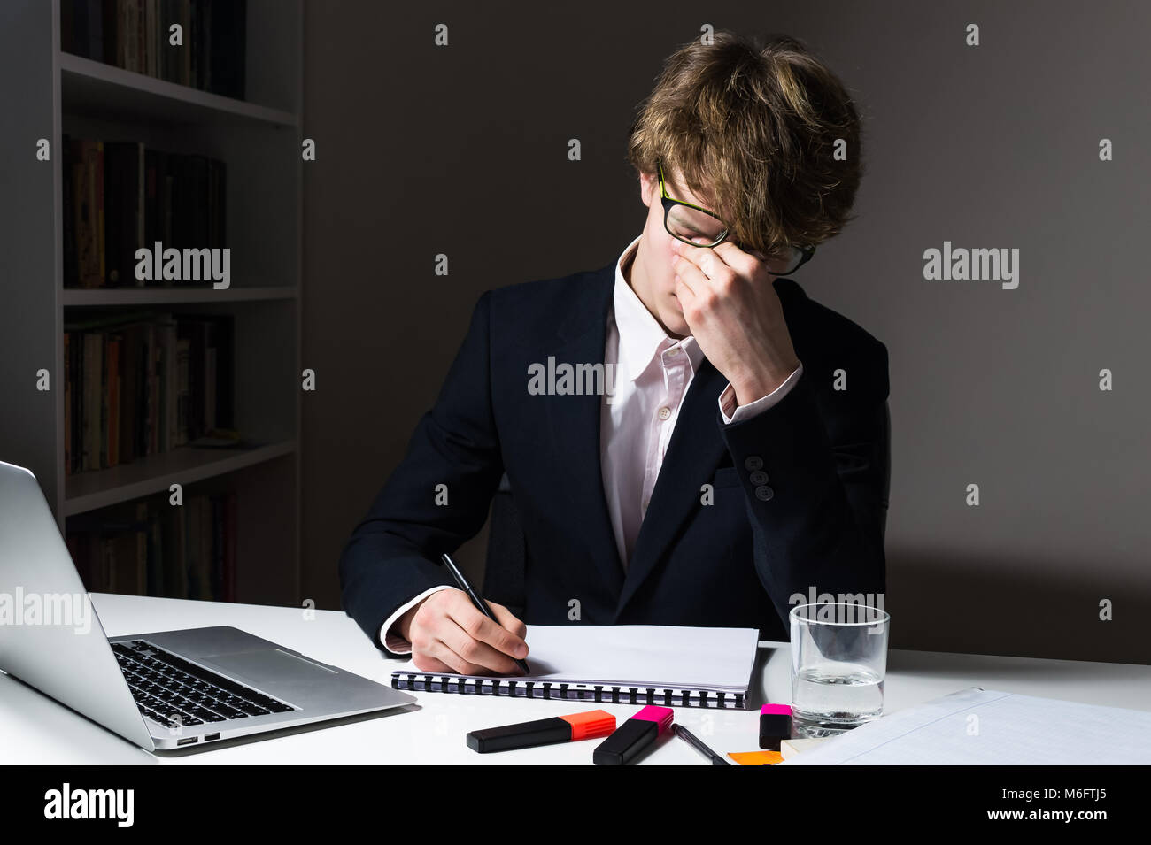 Tired young businessman rubs his eyes at workplace. - Stock Image