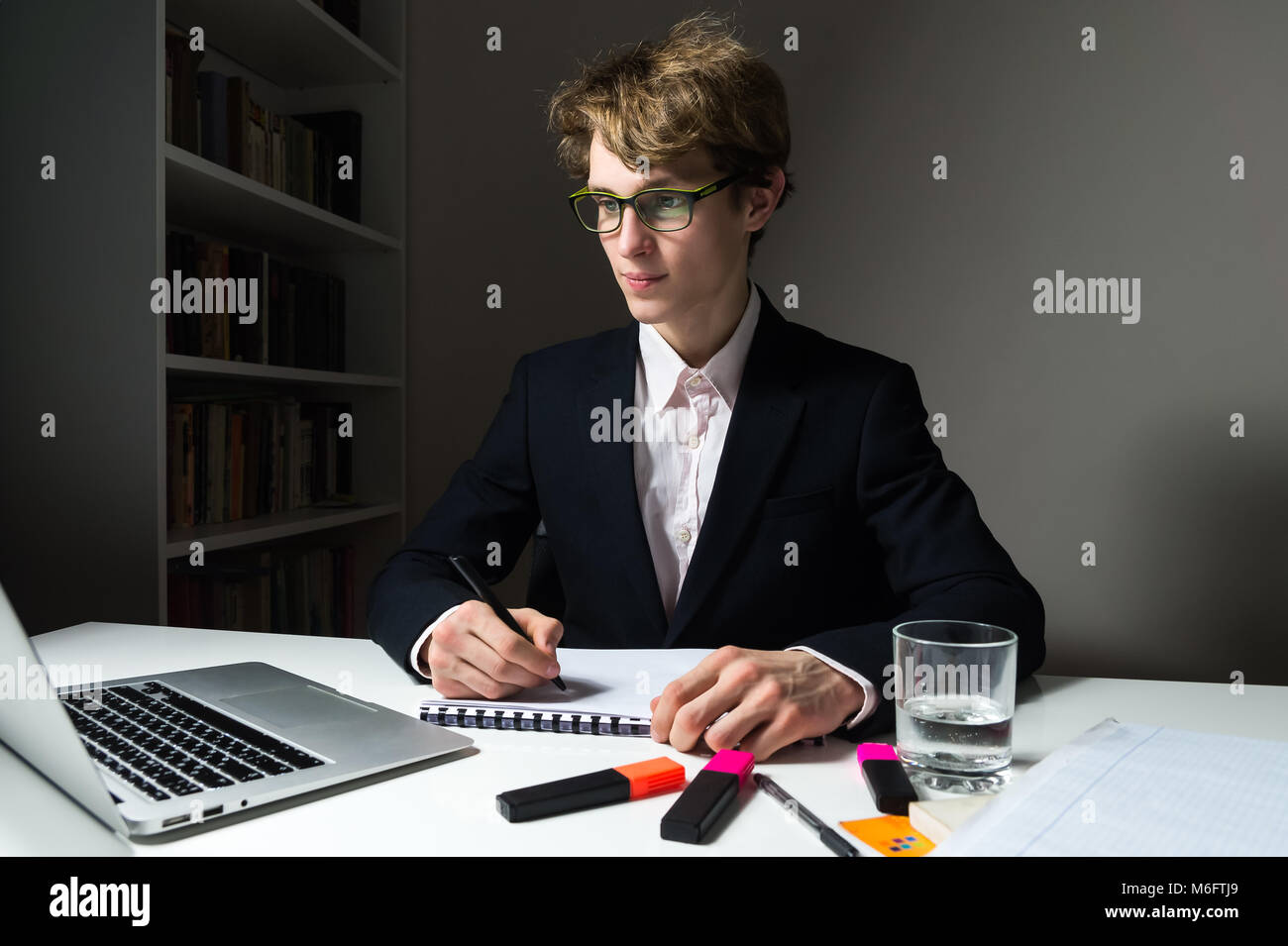 Determined and confident young businessman works late hours in office on project to meet deadline. - Stock Image