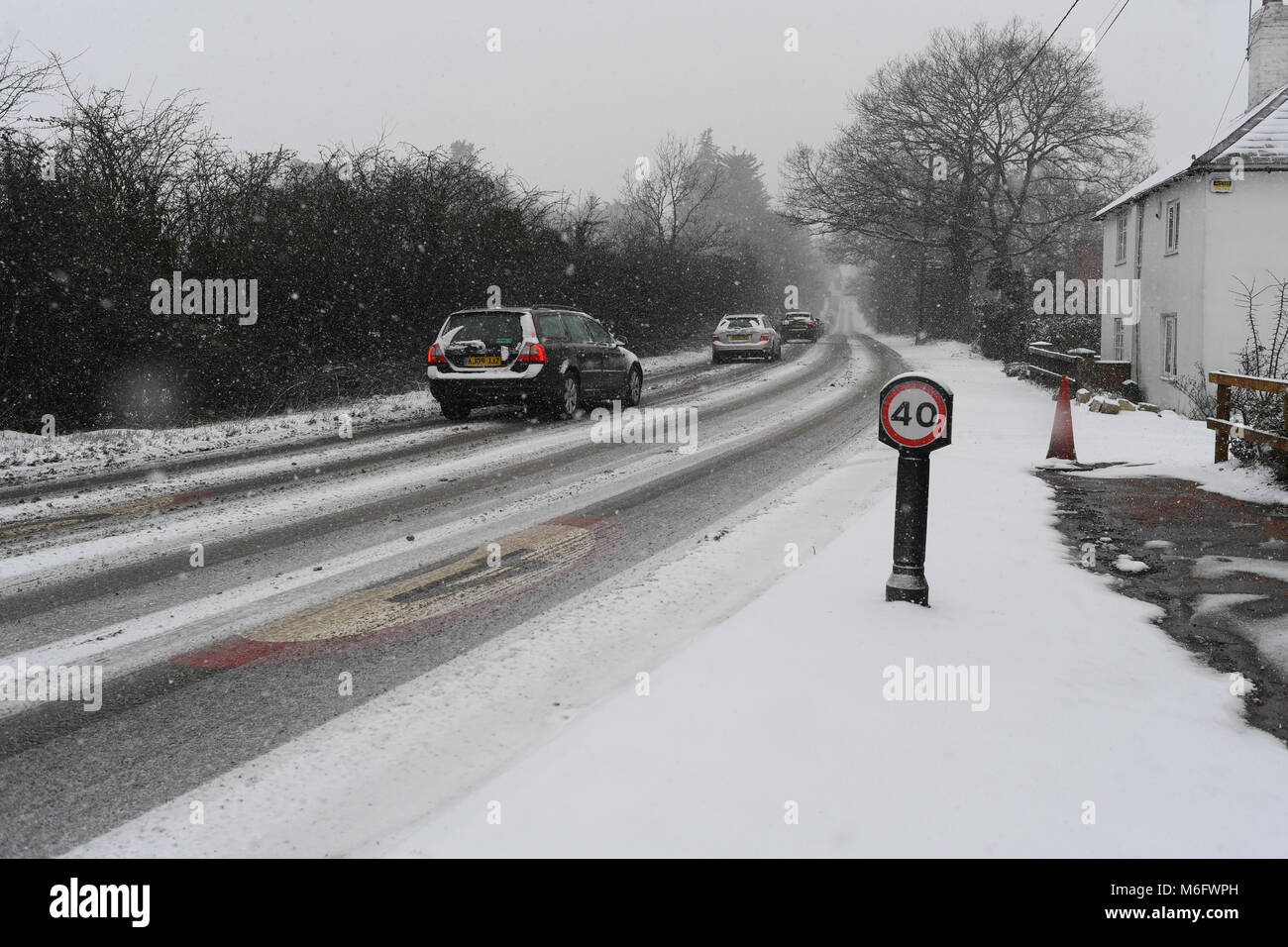 Snow covered 40mph sign on the A36 towards Salisbury England in tricky driving conditions in the snow of March 2018. - Stock Image