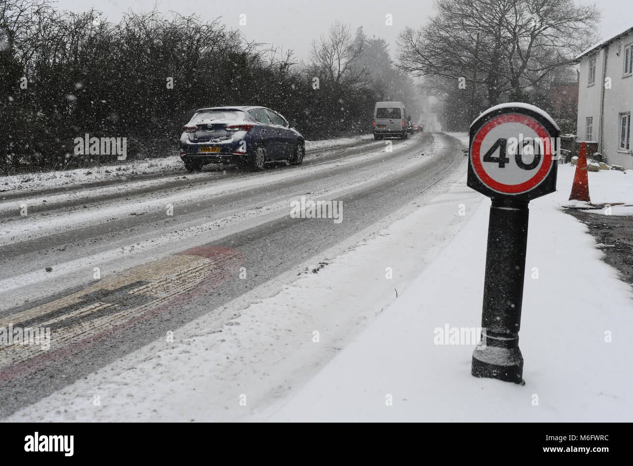Snow covered 40mph sign on the A36 towards Salisbury England in tricky driving conditions in the snow of March 2018. Stock Photo