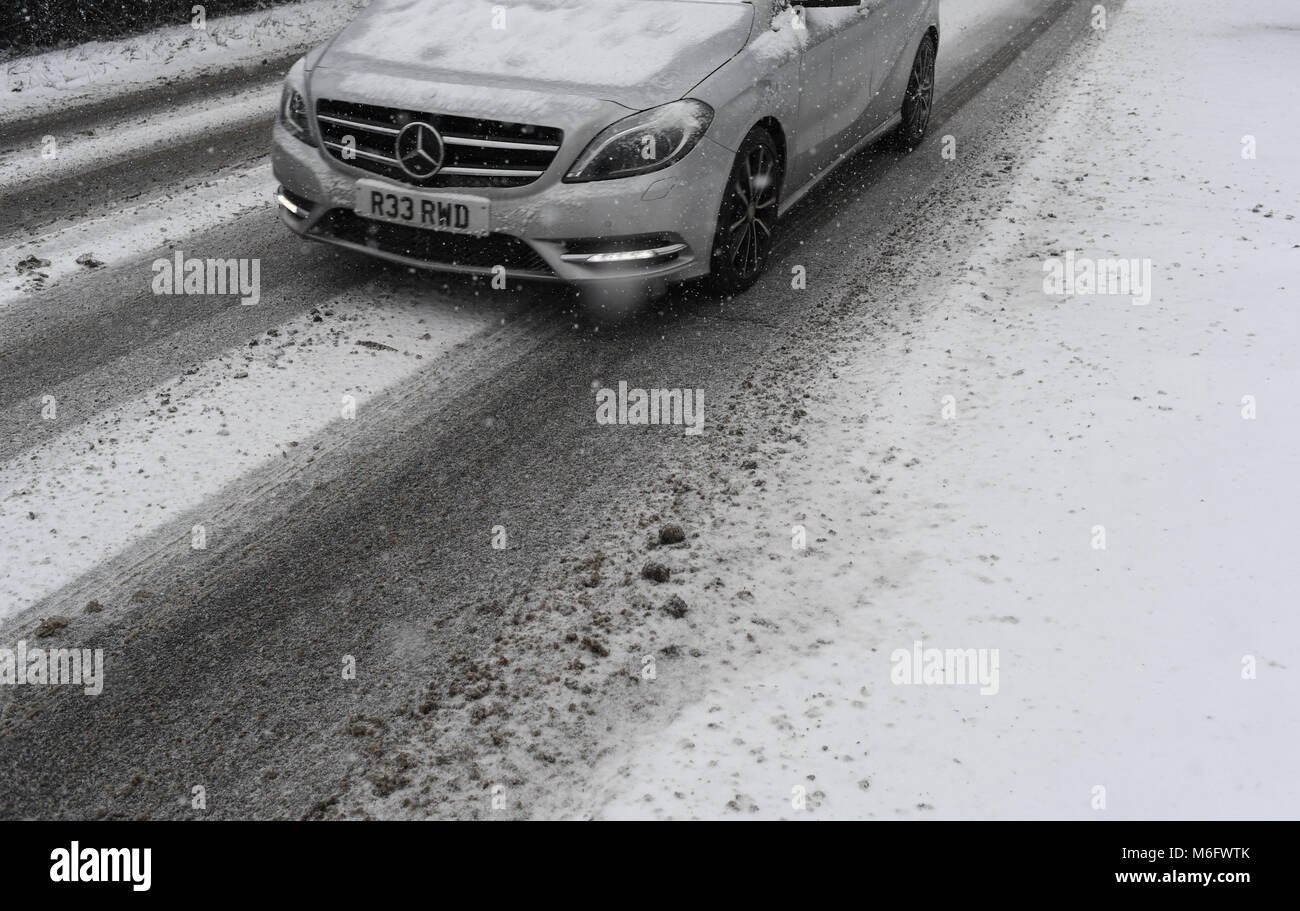 A close up of the wheels and bonnet of a silver mercedes car driving in the snow covered road on the A36. - Stock Image