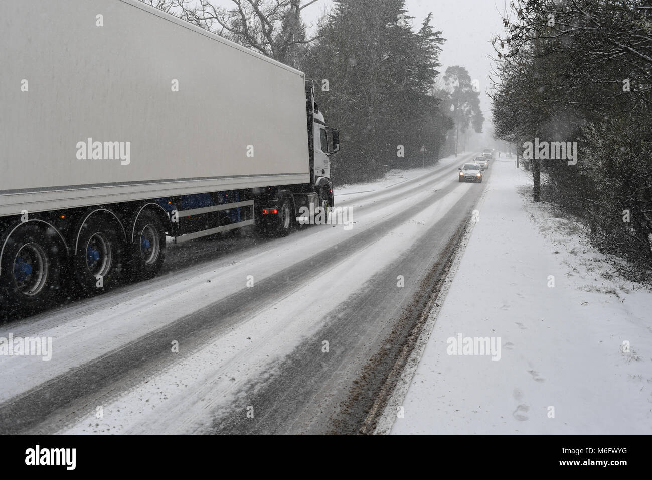 A unmarked logo free white truck drives along the treacherous snow covered A36 during the March 2018 snow storms - Stock Image