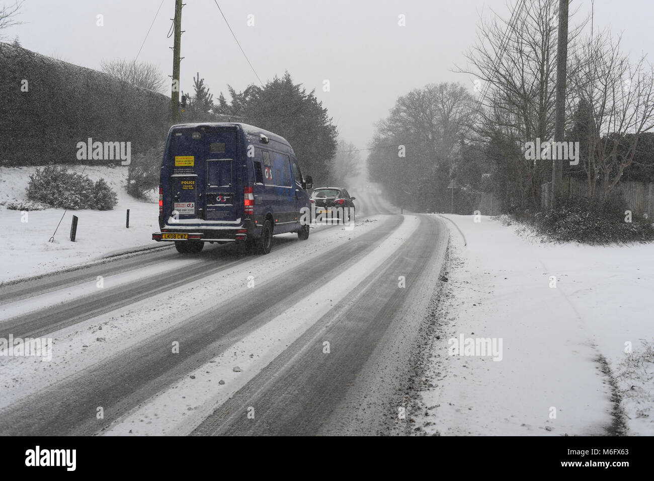 A G4S security money van driving in the snow in treacherous conditions. - Stock Image