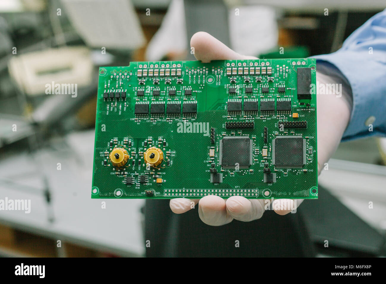 Technician with computer circuit board with chips. Spare parts and components for computer equipment. Production - Stock Image
