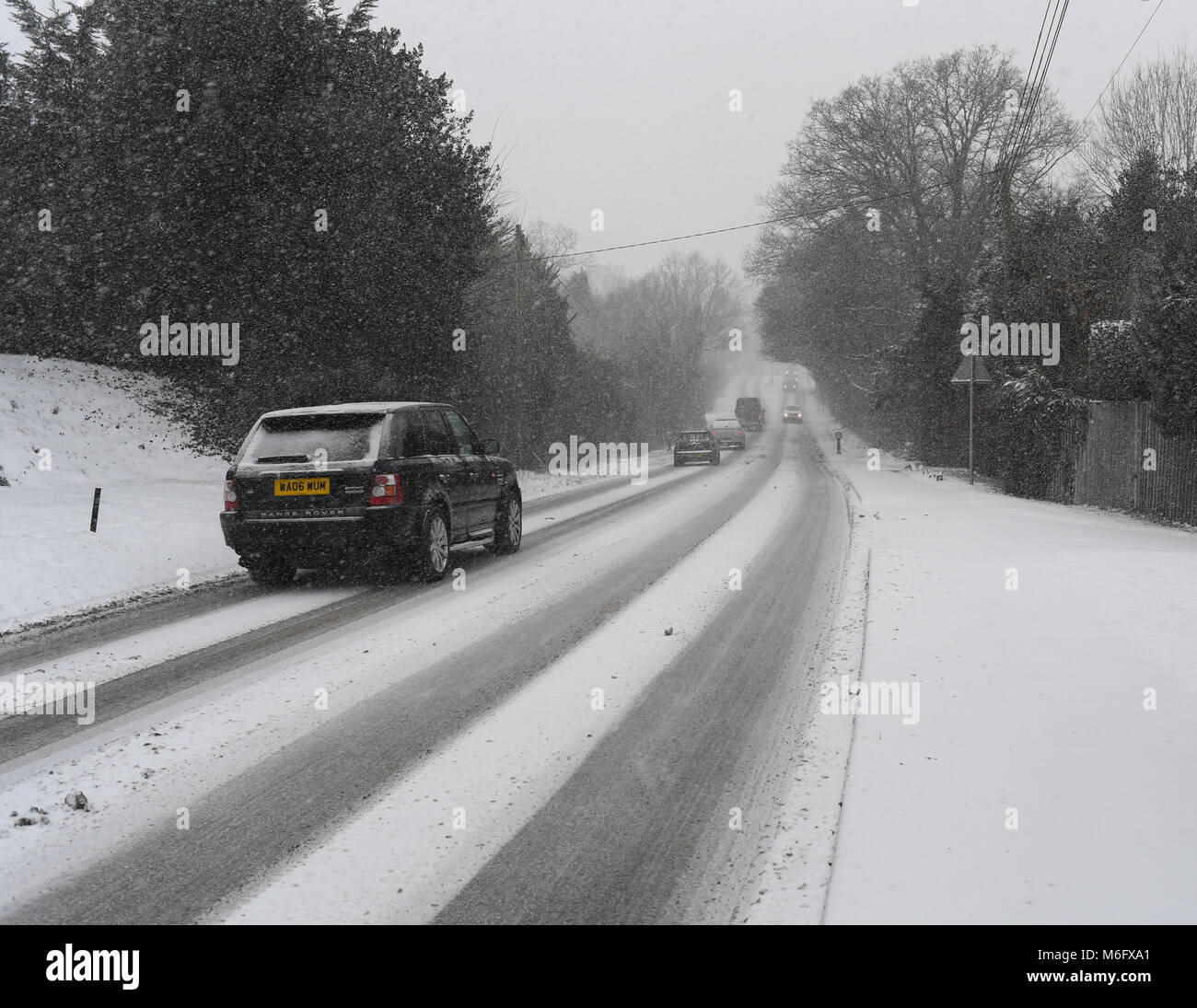A four wheel drive black Range Rover makes its way along a snow covered A36 main road towards Salisbury in treacherous - Stock Image