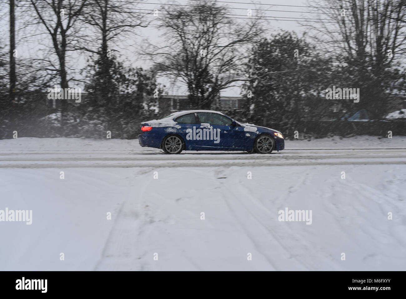 A blue BMW 3 series drives along the snow covered A36 towards Southampton in tricky driving conditions. Stock Photo