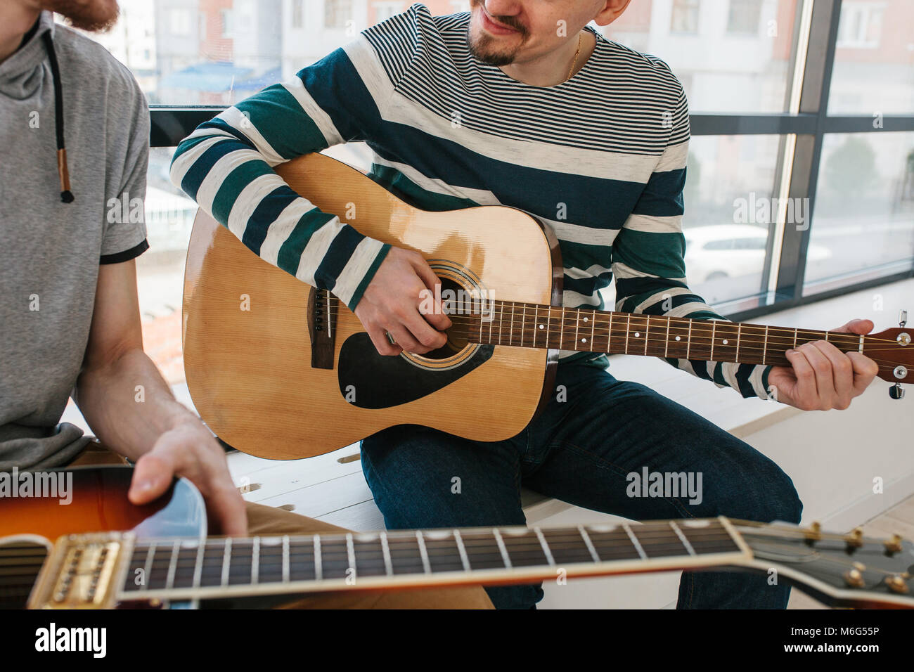 Learning to play the guitar. Music education and extracurricular lessons. Stock Photo