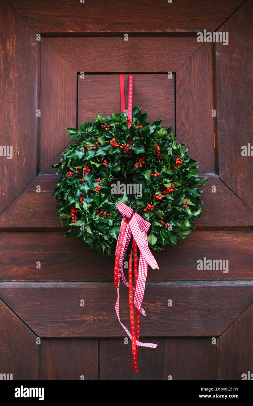 Christmas decoration of the door with a beautiful traditional wreath. Celebrating Christmas, decorating the house. - Stock Image