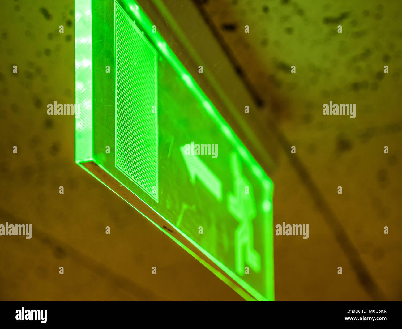 Indoor view green emergency fire exit sign on ceiling. - Stock Image