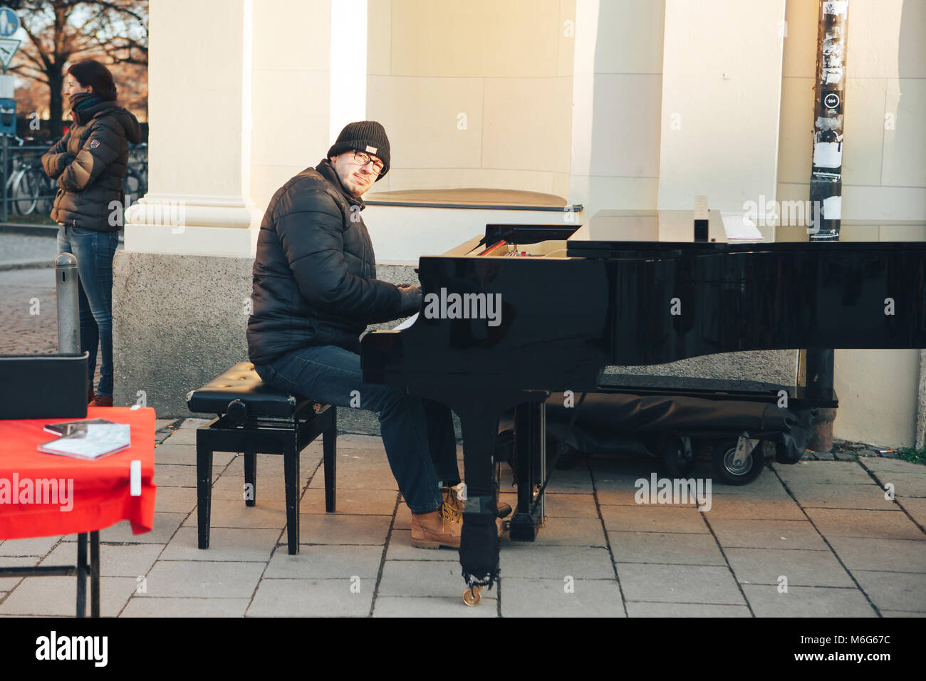 Munich, Germany, December 29, 2016: a street musician playing the piano. Entertainment of tourists in Europe. Street - Stock Image